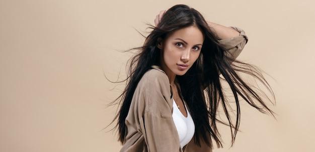 Ritratto di una bella ragazza mora con capelli lunghi sani sul beige