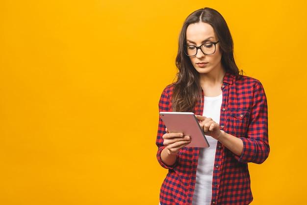 Ritratto di donna seria fiduciosa abbastanza affascinante in casual avendo tablet nelle mani