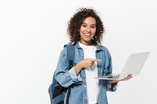 Ritratto di una ragazza africana casual piuttosto allegra che porta uno zaino in piedi isolato su un muro bianco, con in mano un computer portatile