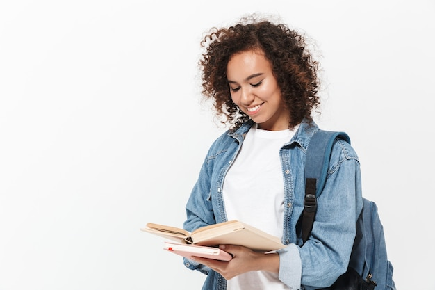 Ritratto di una ragazza africana casual piuttosto allegra che porta uno zaino in piedi isolato su un muro bianco, con in mano libri di testo