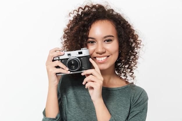 Ritratto di una ragazza africana casual piuttosto allegra in piedi isolata su un muro bianco, con in mano una macchina fotografica