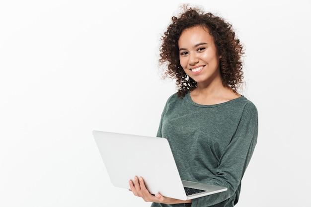 Ritratto di una ragazza africana casual piuttosto allegra in piedi isolata su un muro bianco, lavorando su un computer portatile