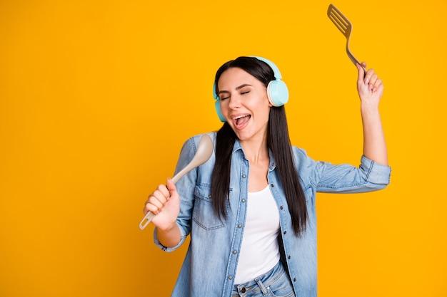 Ritratto di una ragazza sognante piuttosto allegra che ascolta lo stereo usando un cucchiaio come il microfono