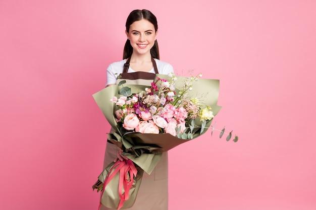 Ritratto del proprietario di un negozio di ragazza piuttosto allegro che tiene in mano un mazzo di fiori