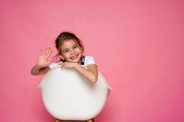 Ritratto di una ragazza abbastanza allegra che saluta con un saluto isolato su sfondo rosa