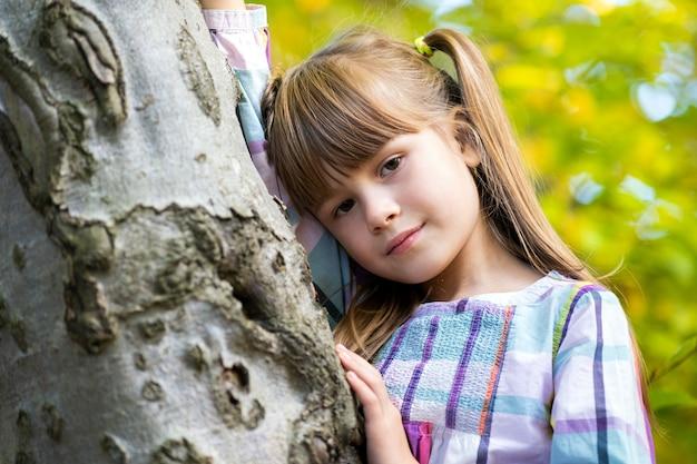 Ritratto di ragazza graziosa del bambino che si appoggia a un tronco d'albero in autunno parco rilassante