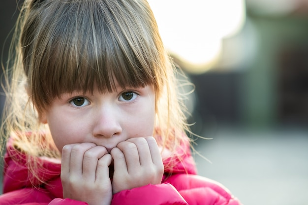Ritratto di una ragazza graziosa del bambino che fa espressione shoked stupita sul suo fronte all'aperto.