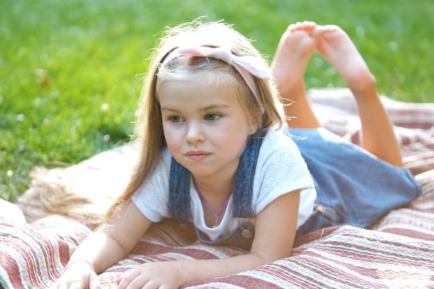 Ritratto di ragazza graziosa del bambino che riposa all'aperto nel parco estivo