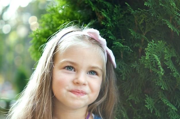 Ritratto della ragazza graziosa del bambino che sta all'aperto nel parco di estate.