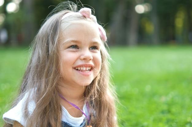 Ritratto della ragazza graziosa del bambino nel parco di estate che sorride felicemente.