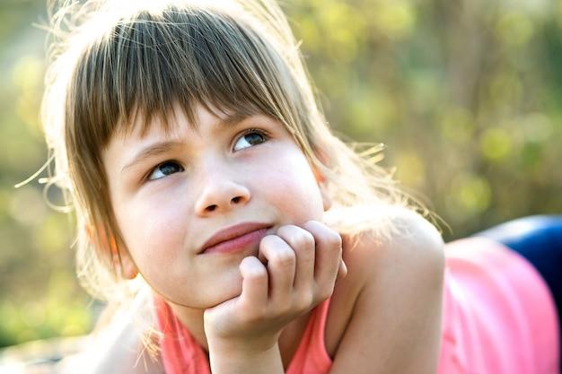 Ritratto della ragazza graziosa del bambino con gli occhi grigi e capelli biondi lunghi che si appoggia sulle sue mani che sorridono felicemente all'aperto su sfondo luminoso sfocato. ragazzo carino femmina nella calda giornata estiva fuori.