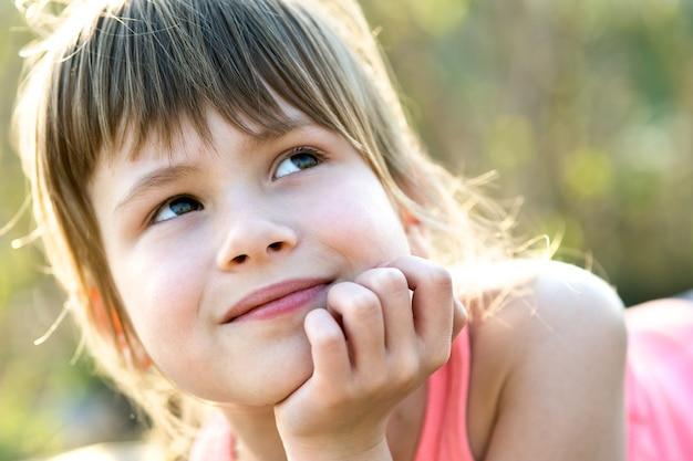 Ritratto della ragazza graziosa del bambino con gli occhi grigi e capelli biondi lunghi che si appoggia sulle sue mani che sorridono felicemente all'aperto