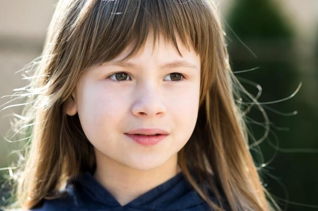 Ritratto della ragazza graziosa del bambino con gli occhi grigi e capelli biondi lunghi all'aperto su sfondo luminoso sfocato. bambino femminile sveglio il giorno di estate caldo fuori.