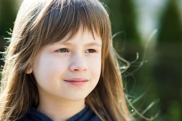 Ritratto di ragazza graziosa del bambino con gli occhi grigi e capelli lunghi biondi all'aperto su sfondo luminoso sfocato.