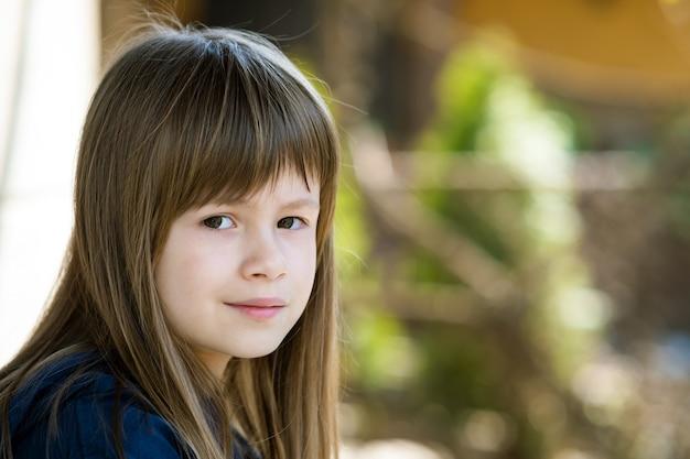 Ritratto di ragazza graziosa bambino con occhi grigi e capelli lunghi biondi all'aperto su sfocato luminoso