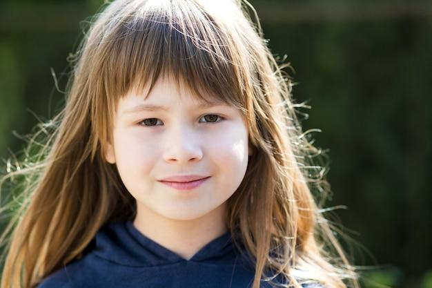 Ritratto di ragazza graziosa del bambino con gli occhi grigi e capelli lunghi biondi sorridente all'aperto su sfondo luminoso sfocato. ragazzo carino femmina nella calda giornata estiva fuori.