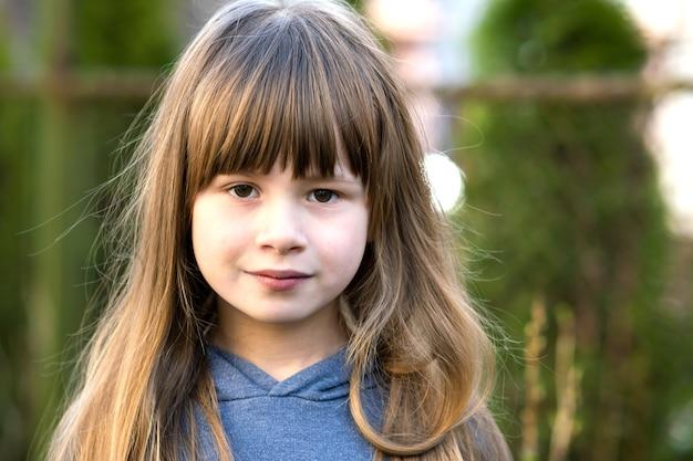Ritratto della ragazza graziosa del bambino con gli occhi grigi e capelli biondi lunghi che sorridono all'aperto