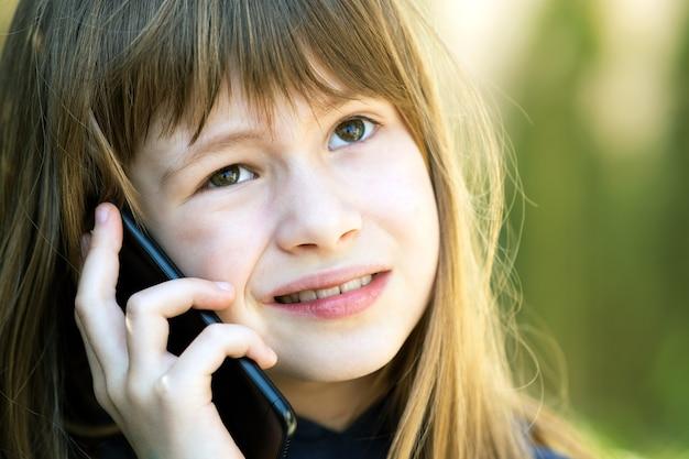 Ritratto di ragazza graziosa bambino con i capelli lunghi, parlando al cellulare. piccolo bambino femminile che comunica tramite smartphone
