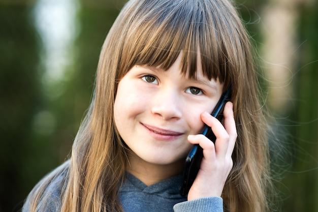 Ritratto della ragazza graziosa del bambino con capelli lunghi che comunicano sul telefono cellulare.