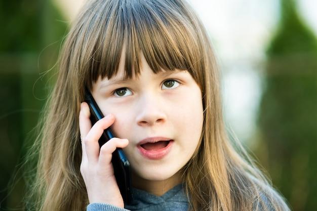 Ritratto di ragazza graziosa bambino con i capelli lunghi, parlando al cellulare