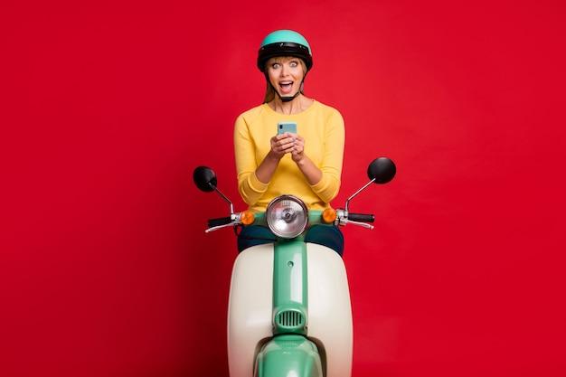 Ritratto di ragazza abbastanza eccitata che si siede sul ciclomotore usando la faccia pazza delle cellule