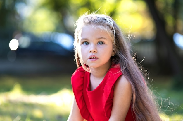 Ritratto di ragazza bambino abbastanza alla moda in abito rosso godendo una calda giornata estiva di sole.