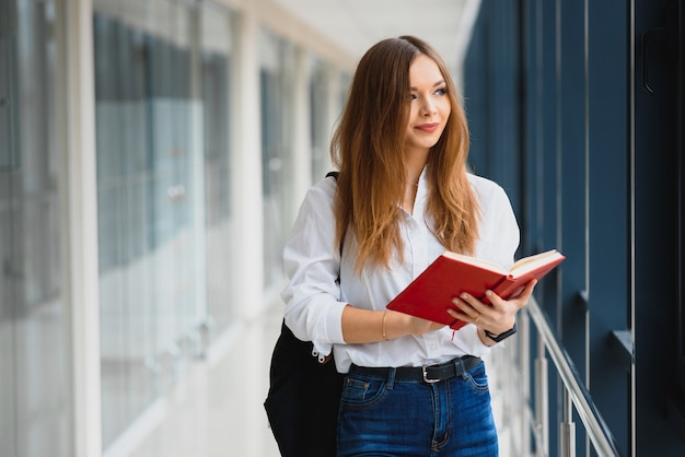 Ritratto di una bella studentessa con libri e uno zaino nel corridoio dell'università