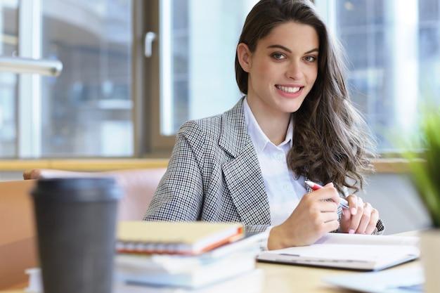 Ritratto di una bella studentessa con laptop in biblioteca.