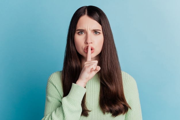 Ritratto di una bella ragazza che copre le labbra con le dita ti chiede di stare tranquillo in posa sul muro verde acqua