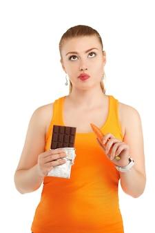 Ritratto di una bella ragazza che ha un dilemma con la sua dieta