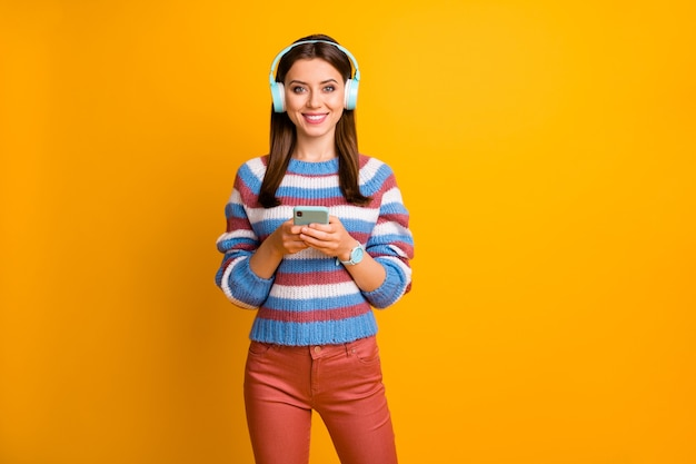 Il ritratto della ragazza graziosa che tiene nelle mani il telefono ascolta le cuffie di musica