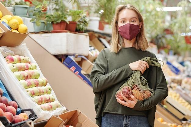 Ritratto di bella ragazza in maschera che tiene un sacchetto netto di prodotti biologici al mercato degli agricoltori durante il coronavirus