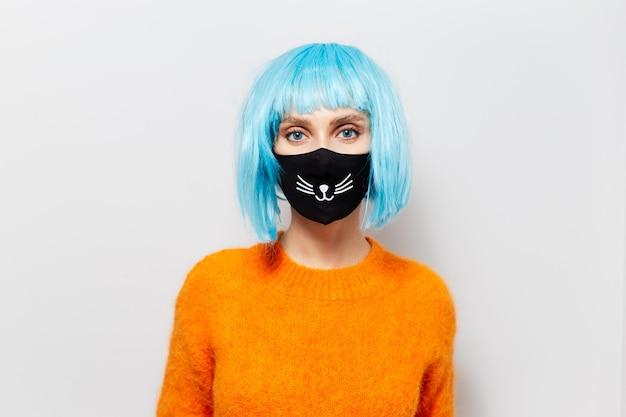 Ritratto di una bella ragazza in maglione arancione con i capelli blu che indossa una maschera medica nera.