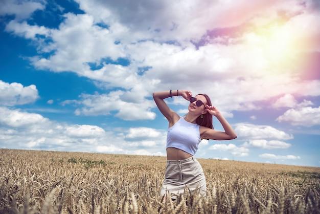 Ritratto di una bella ragazza in posa sullo sfondo di un'ora legale di un campo agricolo