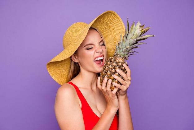 Ritratto della ragazza graziosa che assaggia le ananas fresche isolate su viola