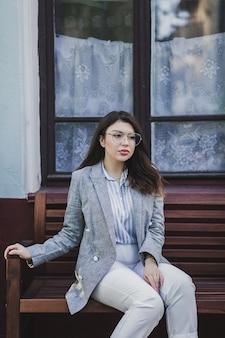 Ritratto di una bella ragazza con lunghi capelli ricci seduti in città. indossa una giacca elegante.