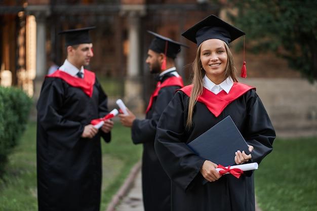 Ritratto di bella donna laureata in abito di laurea con diploma nelle sue mani.