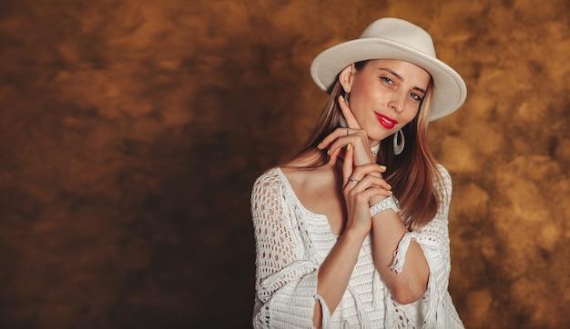La giovane donna alla moda abbastanza felice del ritratto con capelli biondi in vestiti bianchi e cappello su fondo oro esamina la macchina fotografica con soddisfazione. concetto di un ritratto emotivo. copia spazio per il sito