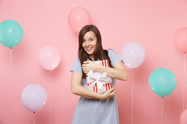 Ritratto di giovane donna piuttosto gioiosa in abito blu che tiene e abbraccia scatola rossa con regalo presente su sfondo rosa pastello con mongolfiere colorate. festa di compleanno, persone sincere emozioni.