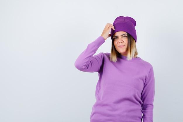Ritratto di bella signora con la mano sulla testa in maglione, berretto e guardando la vista frontale smemorata