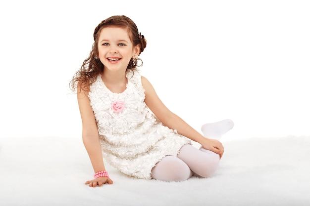 Ritratto di una ragazza di moda abbastanza divertente che si siede su un soffice tappeto sul pavimento e si diverte contro il bianco
