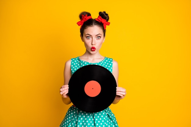 Ritratto di bella ragazza stupita che tiene in mano le labbra del broncio del disco in vinile isolate su uno sfondo di colore giallo vivido