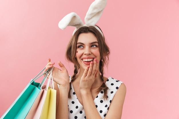 Ritratto di una ragazza abbastanza adorabile che indossa le orecchie del coniglietto in piedi isolato, portando le borse della spesa
