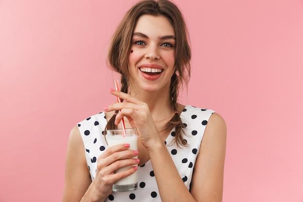 Ritratto di una ragazza abbastanza adorabile che indossa un abito in piedi isolato, bere latte
