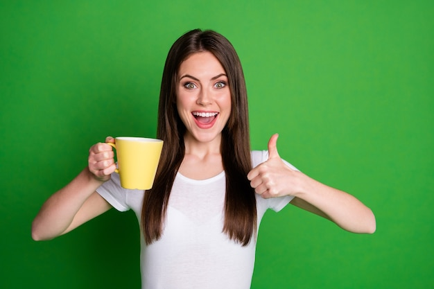 Il ritratto di una ragazza bruna eccitata piuttosto positiva che beve cacao mostra il pollice in alto isolato su uno sfondo di colore verde