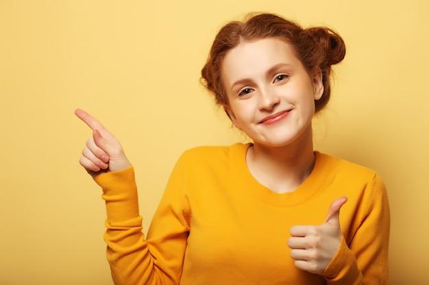 Ritratto di una ragazza piuttosto redhair che punta il dito lontano su sfondo giallo