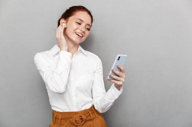 Ritratto di una bella donna d'affari dai capelli rossi 20s che indossa auricolari che tiene e guarda lo smartphone in ufficio isolato su grigio