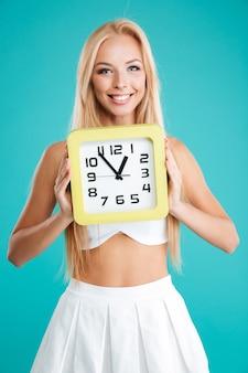 Ritratto di una ragazza abbastanza sorridente che tiene l'orologio da parete e guarda la telecamera isolata sullo sfondo blu