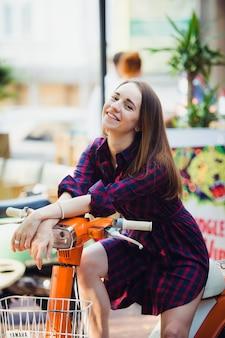 Ritratto di ragazza sorridente graziosa su scooter