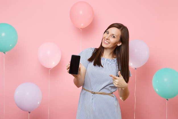 Ritratto di donna felice abbastanza sorridente che indossa abito blu tenendo il dito indice puntato sul telefono cellulare con schermo vuoto vuoto su sfondo rosa con mongolfiere colorate. festa di compleanno.